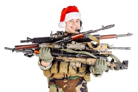 soldier with rifle wearing Santa claus cup and holding cardbox i