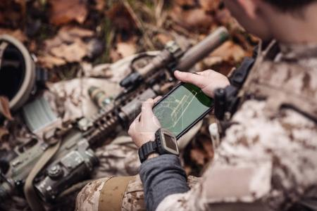soldiers holding gps in hand and determines the location of coor