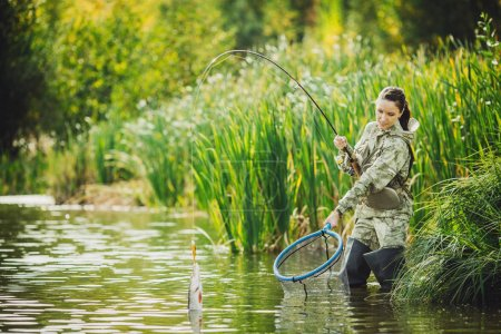 pretty woman fishes on the river. Spinning equipment, angling, f