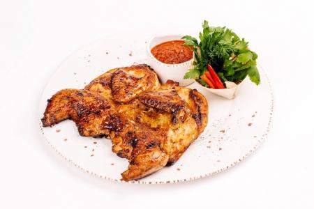 Grilled chicken Tabaka with sauce on a plate on white background