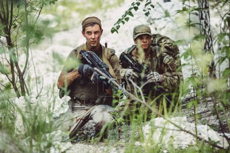 British Army sniper during the military operation in the forest. war, army, technology and people concept.