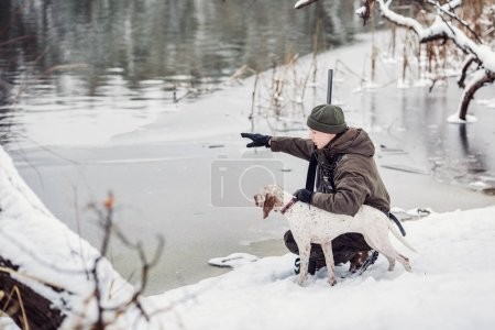 hunter and his Bourbonnais Pointing Dog by a river in the winter