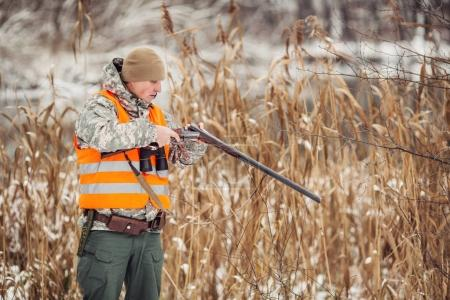 hunter loading rifle in a winter forest. Bushcraft, hunting and