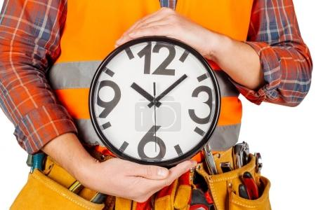 male builder with big clock over white wall background. repair, construction, building, people and maintenance concept.