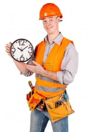 builder in a helmet holding big clock and looking at camera over white wall background. repair, construction, building, people and maintenance concept.