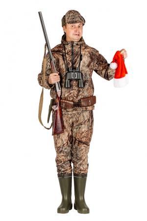 male hunter with double barreled shotgun holding santa hat