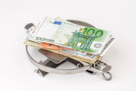 trap with a bundle of EURO isolated on white. financial crime co