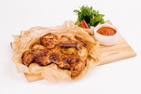 Grilled chicken Tabaka with sauce on a wooden plate on white bac