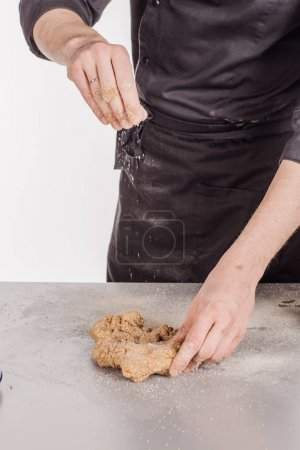 Chef or baker making bread and pouring flour to dough at bakery