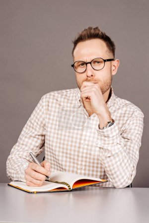 Pensive sad man sitting at the table with notepad over gray background.  facial expressions, feelings, body language, signs. image on a dark studio background.
