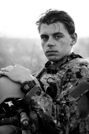 young soldier face with camouflage against a sunset background