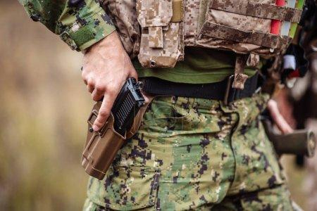Ranger wearing uniform with gun in hand,keep gun in the holster.