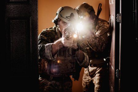 soldiers or private military contractors holding rifle. Image on