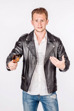 portrait of a young man holding a broken glass bottle in a threatening way Isolated on white background. emotion and people concept.
