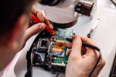 Close up hands of a service worker repairing digital camera.