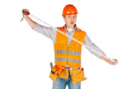 builder in a helmet holding tape-measure in his hands  over white wall background. repair, construction, building, people and maintenance concept.