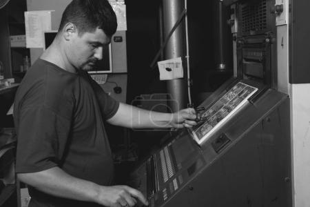 CHISINAU, MOLDOVA - APRIL 26, 2016: Workers in printing house. People working on printing machine in print factory. Industrial workers in Chisinau, Moldova on April 26, 2016