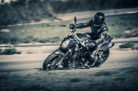 Ulyanovsk, Russia - August 19, 2017. A motorcycle racer on a black classical motorcycle trains on a sports track. Motion blur.