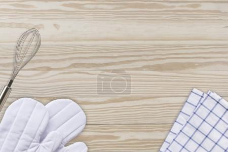 White cooking gloves, Napkin and Egg blender on wood table backg