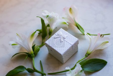 Gift box surrounded with alstroemeria flowers on marble surface