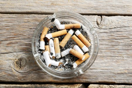 Cigarette butts with ash in ashtray
