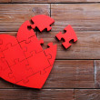 Red puzzle heart on brown wooden background...