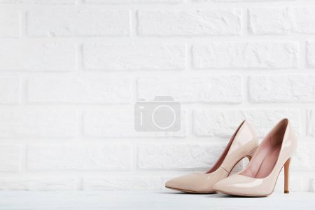 Photo for Pair of female high-heeled shoes on bricks wall background - Royalty Free Image