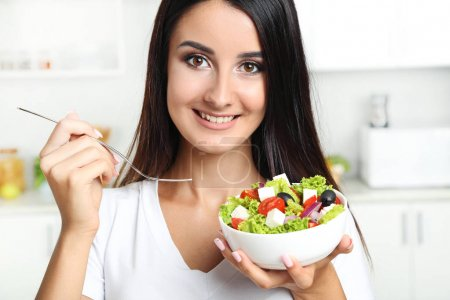 Beautiful young woman eating vegetable salad