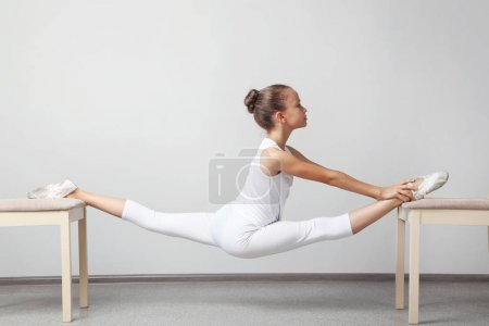 Young girl doing stretching on chairs