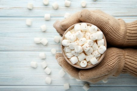 Hand in beige gloves holding cup