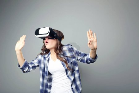 Photo for Young girl in virtual reality goggles on grey background - Royalty Free Image