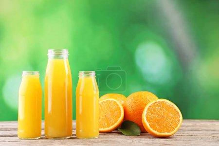Photo pour Bouteilles de jus d'orange sur table en bois - image libre de droit
