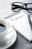 To do list in notepad with cup