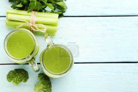 Bottles of juice with broccoli and celery