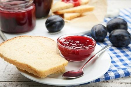 Plum jam in bowl with bread