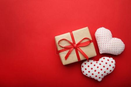 Gift box with fabric hearts on red background