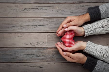 Female and male hand holding red fabric heart on grey background