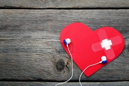 Red paper heart with adhesive bandage and earphones on wooden table