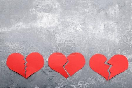 Broken red hearts on grey wooden table