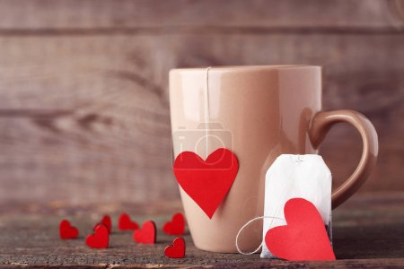 Cup of tea with red hearts and teabag on wooden table