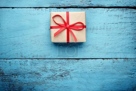 Gift box with red ribbon on blue wooden table