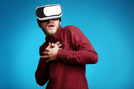 Young man in virtual reality goggles on blue background