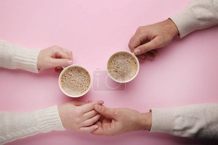 Female and male hand holding each other and cups of coffee