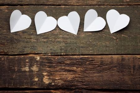 White paper hearts on grey wooden table
