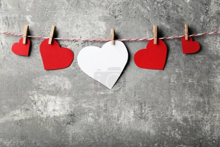 Red and white paper hearts hanging on wooden background