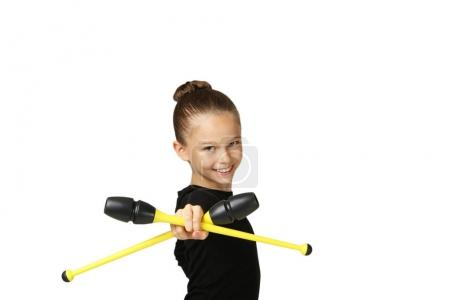 Young girl gymnast with mace on grey background