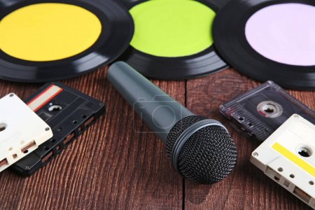 Vinyl records with cassette tapes and microphone on wooden table
