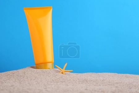 Sunscreen with starfish on beach sand