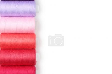 Colourful thread spools on white background