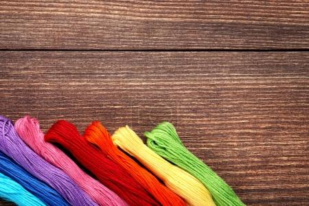 Colourful threads on brown wooden table